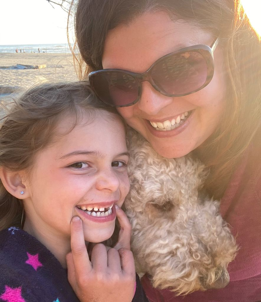 Brooke Hambly, a smiling adult with long brown hair wearing sunglasses, poses with her daughter - whose smile shows a missing front tooth - and their white, fuzzy dog