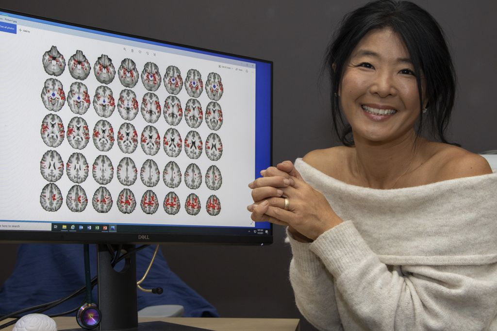 OHSU researcher Milky Kohno, a smiling Asian woman, poses with digital brain scan images