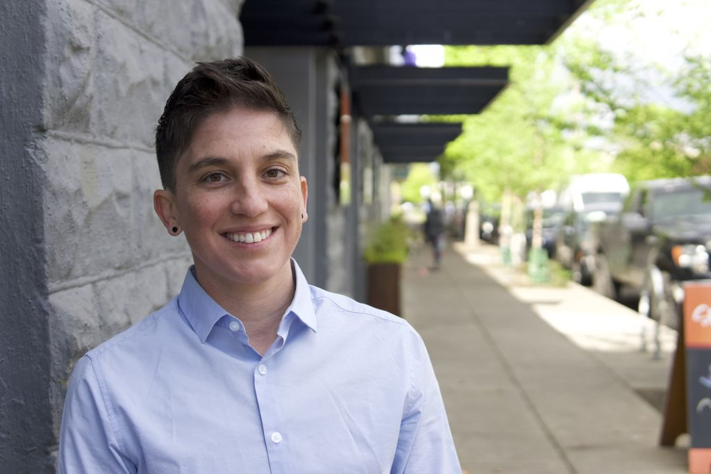 Jae Downing Ph.D., a smiling adult with brown eyes and short, brown hair, stands on a sidewalk leaning against a building