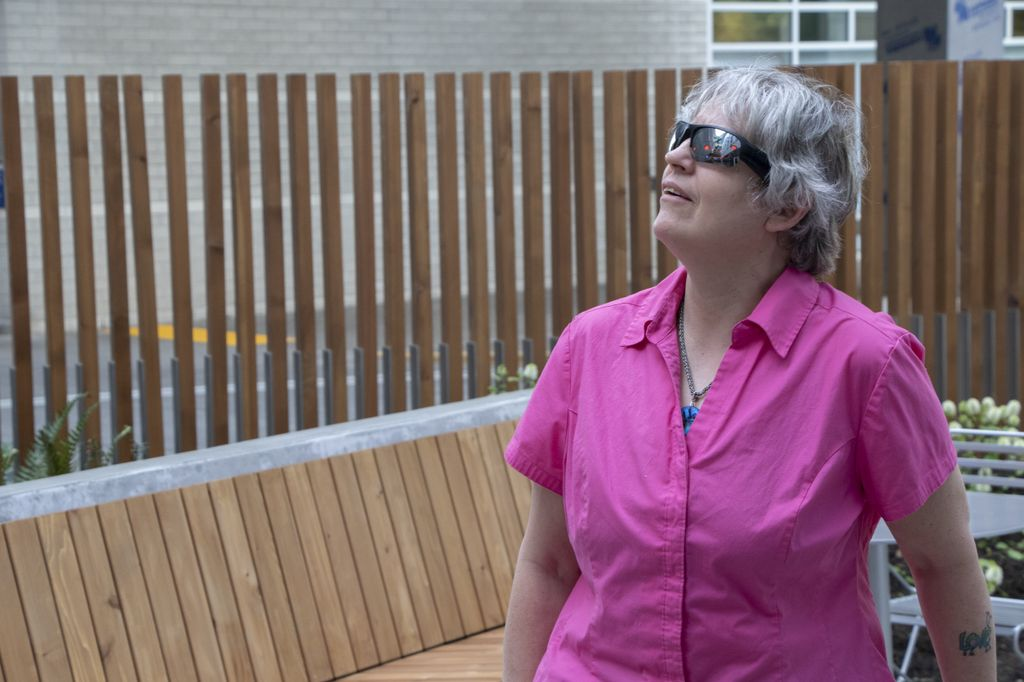 A woman with short, shaggy gray hear wears a bright pink, short-sleeved shirt and a pair of sunglasses as she looks up to the left.