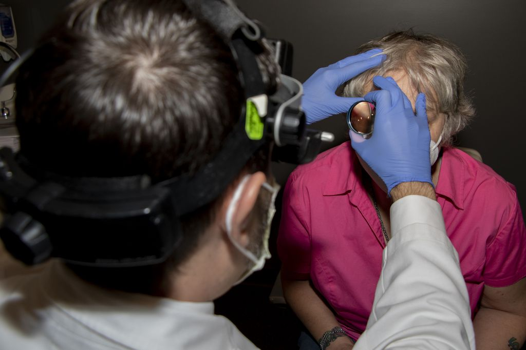 A man places a magnifying device near the eyes of a woman as she looks up at him.