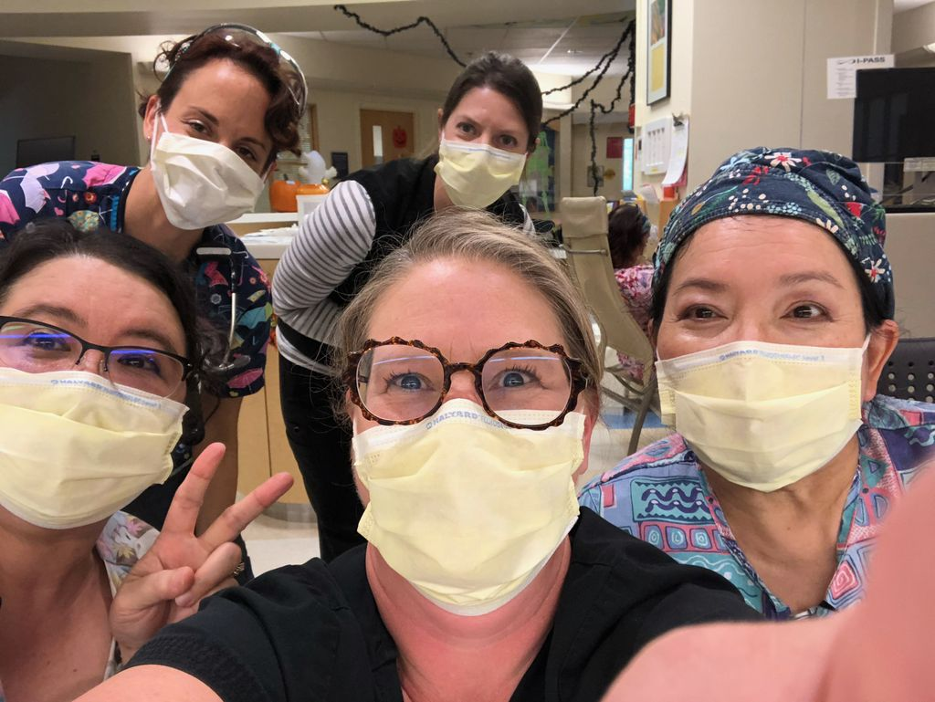 A group of five women wearing face masks smile for a group photo.