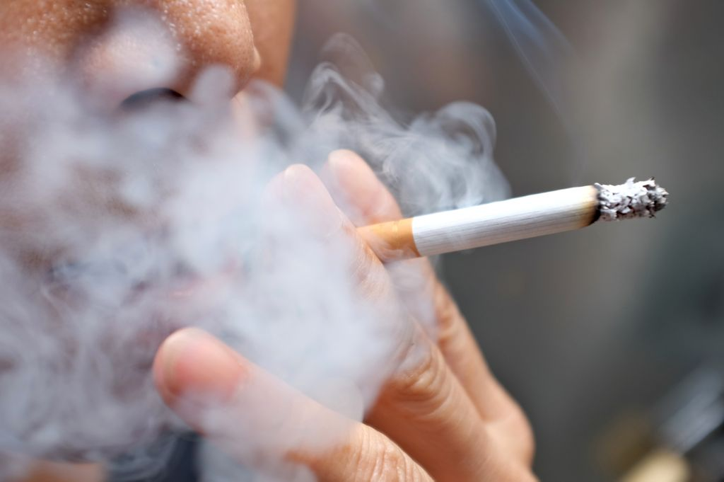 Close up of a person smoking a cigarette (only nose, mouth and hand visible) with smoke around them and a blurred background