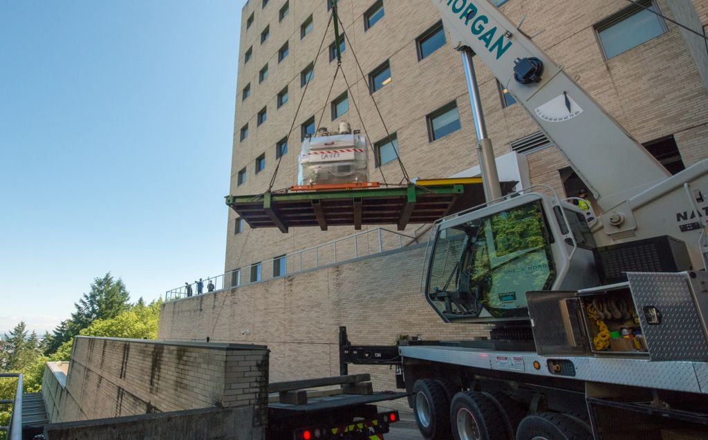 A crane outside of a large medical building hoists a massive magnet through the air.