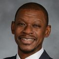 Portrait of Lishomwa Ndhlovu, M.D., Ph.D., a smiling Black man in a suit