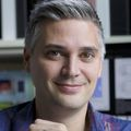Portrait of Jonah Sacha, Ph.D., a grey-haired man sitting in front of a blurry computer monitor