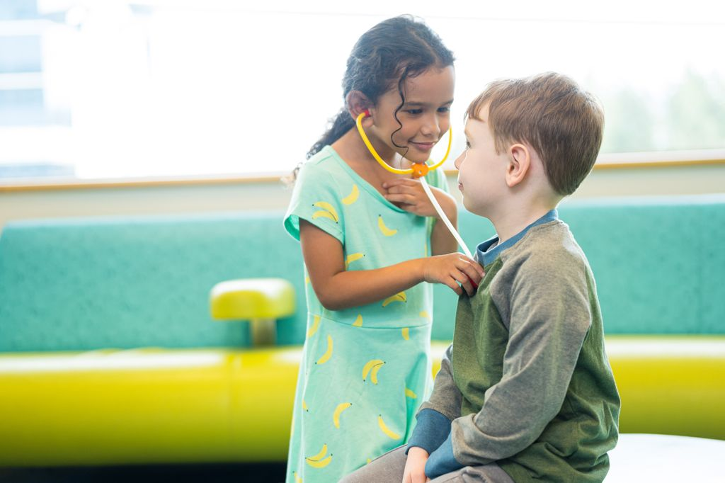 Two children play: a dark-haired girl wearing a toy stethoscope listens to a white boy's heart