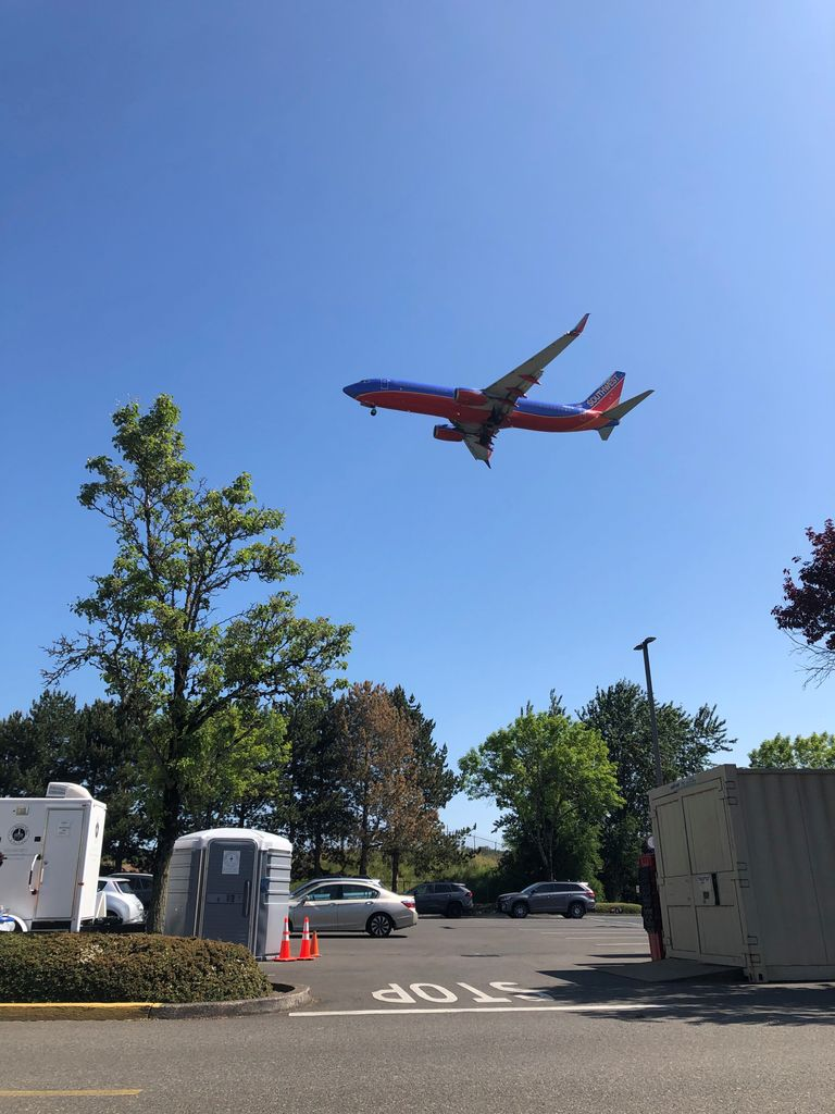 An airplane flying low to the ground has just taken off from the north runway at Portland International Airport. Trees and a parking lot are in the foreground.