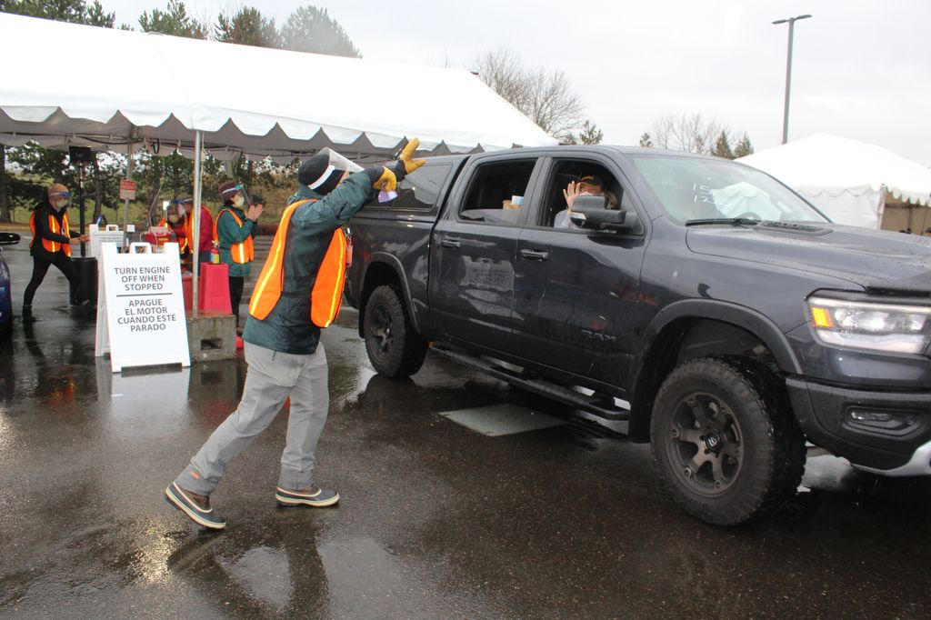 A volunteer in an orange safety vest rings a bell as a black truck leaves the premises with newly-vaccinated occupants.
