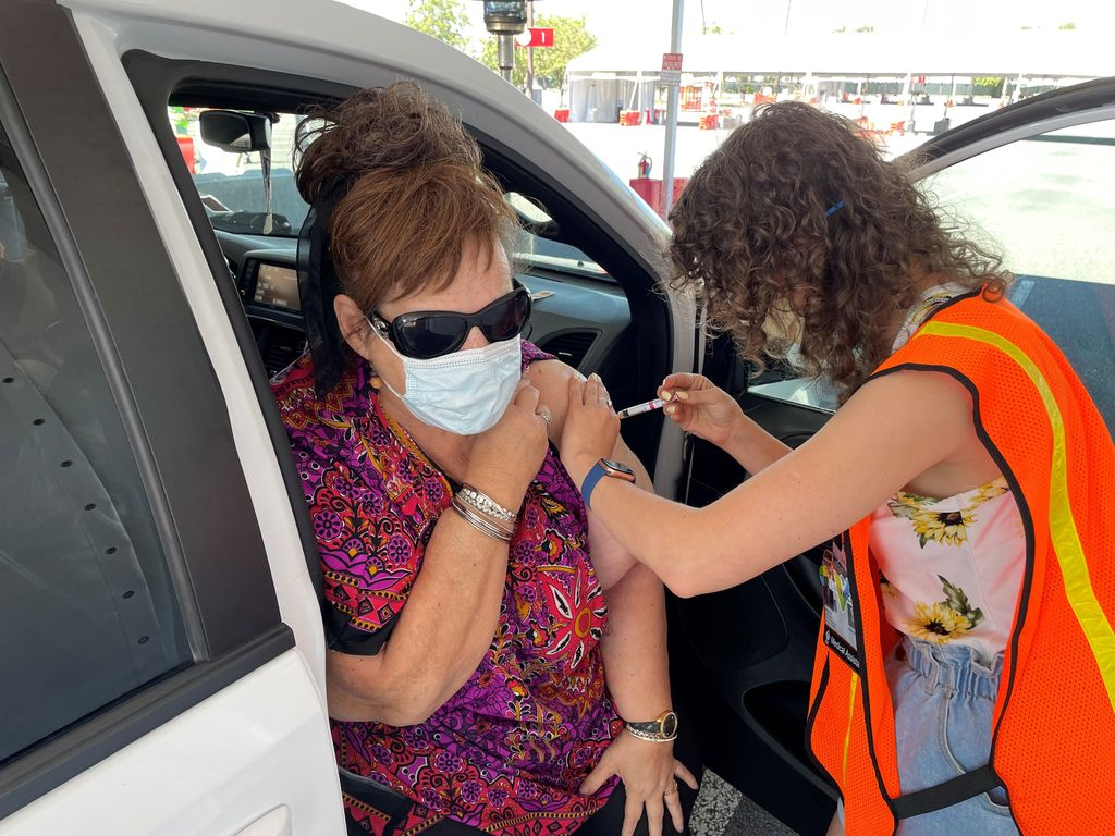 A woman seated on her car's seat exposes her upper arm and receives a vaccine injection from a curly-haired clinician in an orange safety vest.