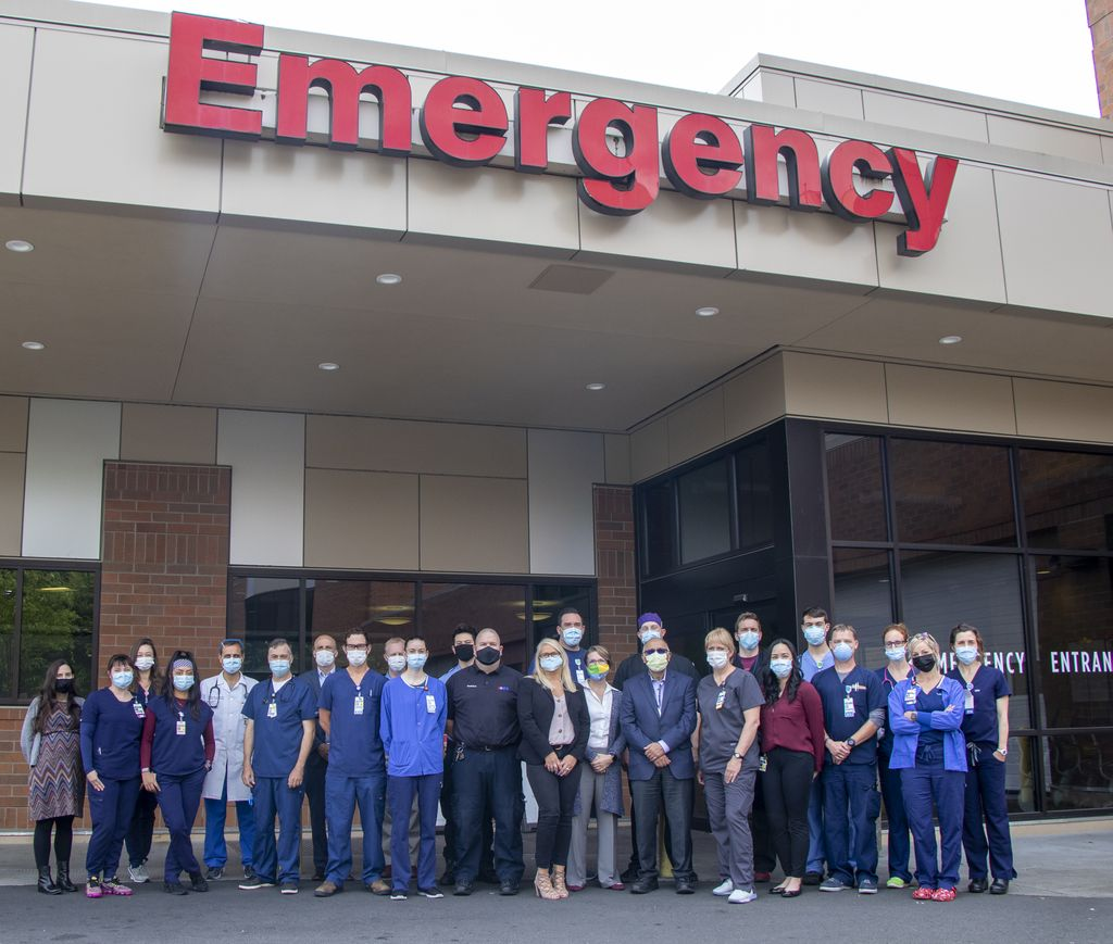 A large group of healthcare and research team members stands outside the Adventist Health Portland Emergency Department.