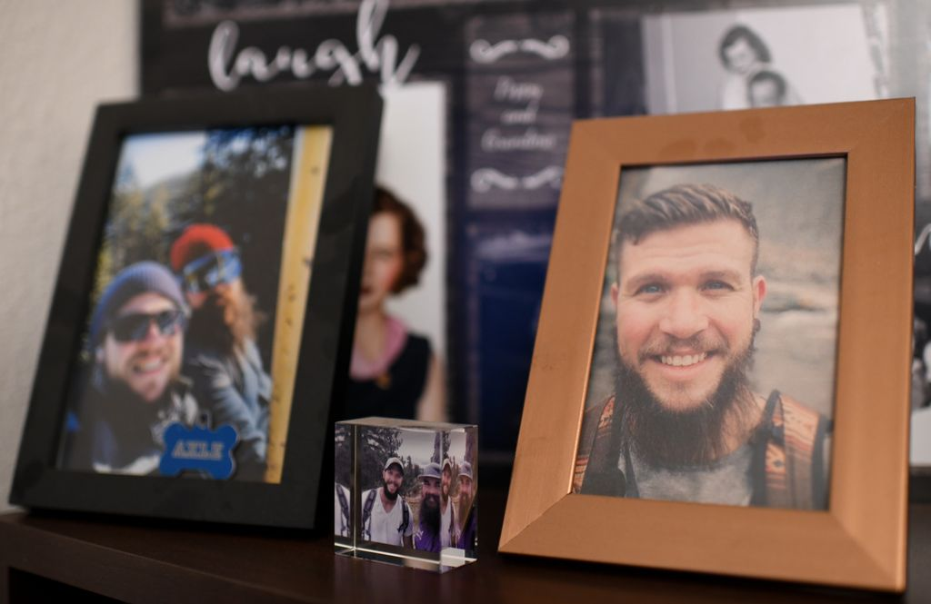 Framed photos of a smiling bearded young man line a countertop.
