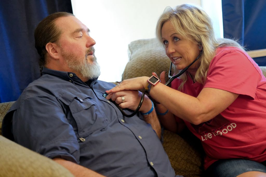 : A woman looks up as she leans into a man's chest, upon which she holds the metal end of a stethoscope.