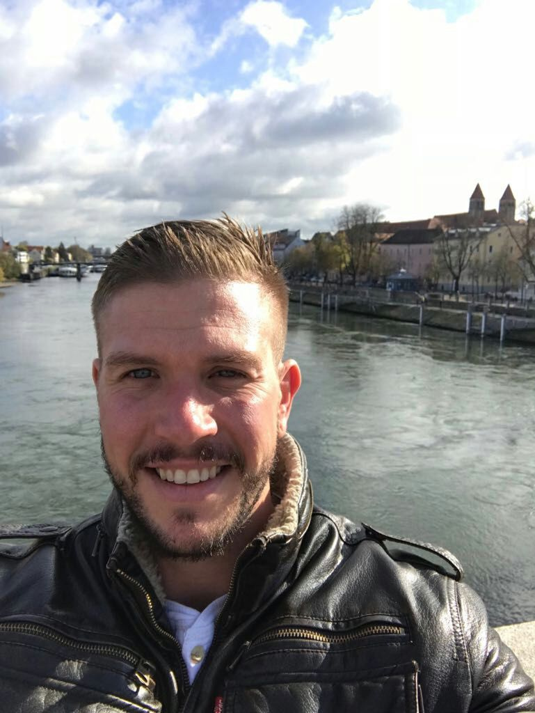 A bearded young man smiles while standing in front of a river.