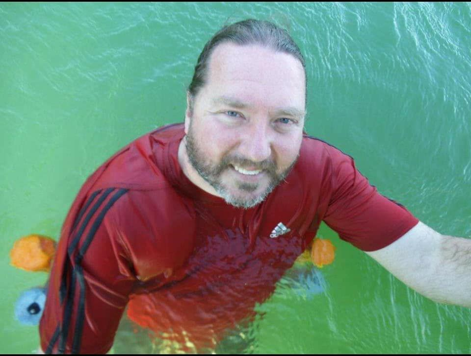 Water drips from a bearded man as he smiles and stands in a body of aquamarine water.
