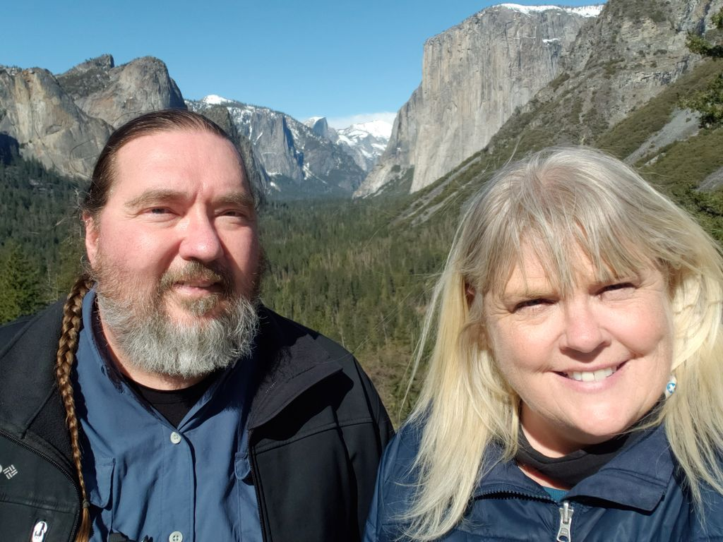 A bearded man and a blonde woman smile as they stand in front of snow-capped mountains and a green forest.