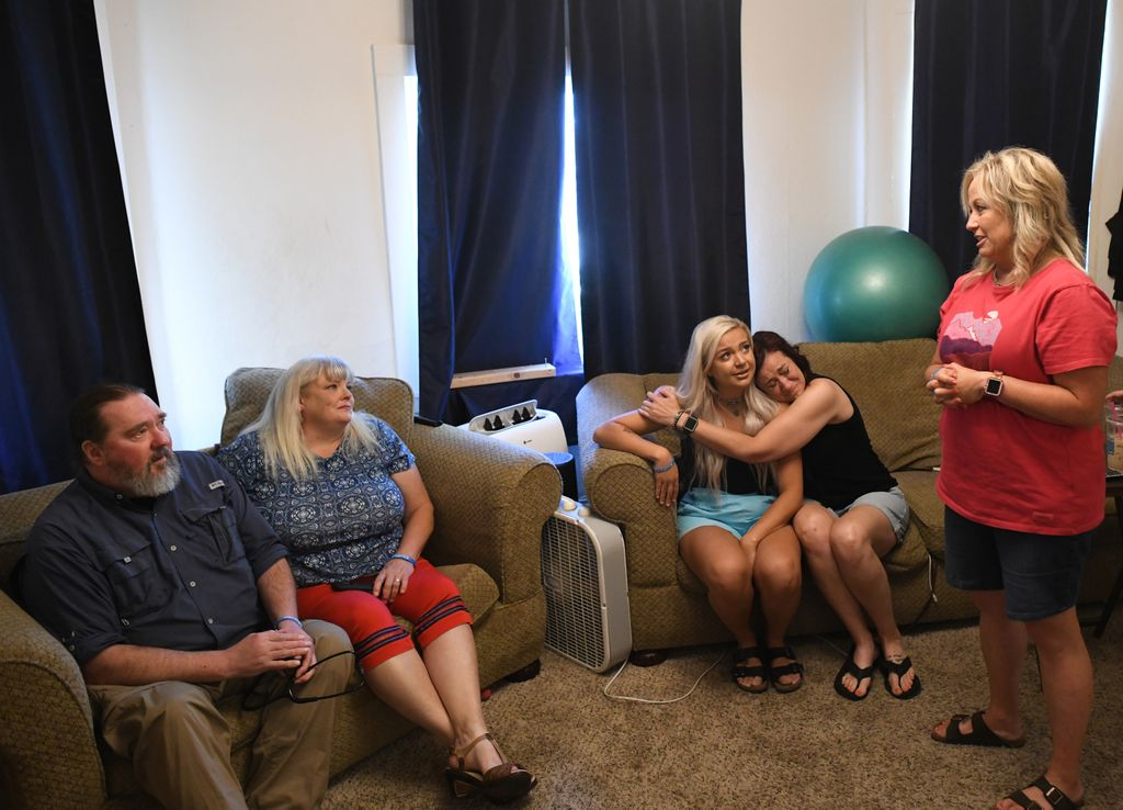 Two women, one crying, embrace while sitting on a couch and others engage in conversation in a living room.