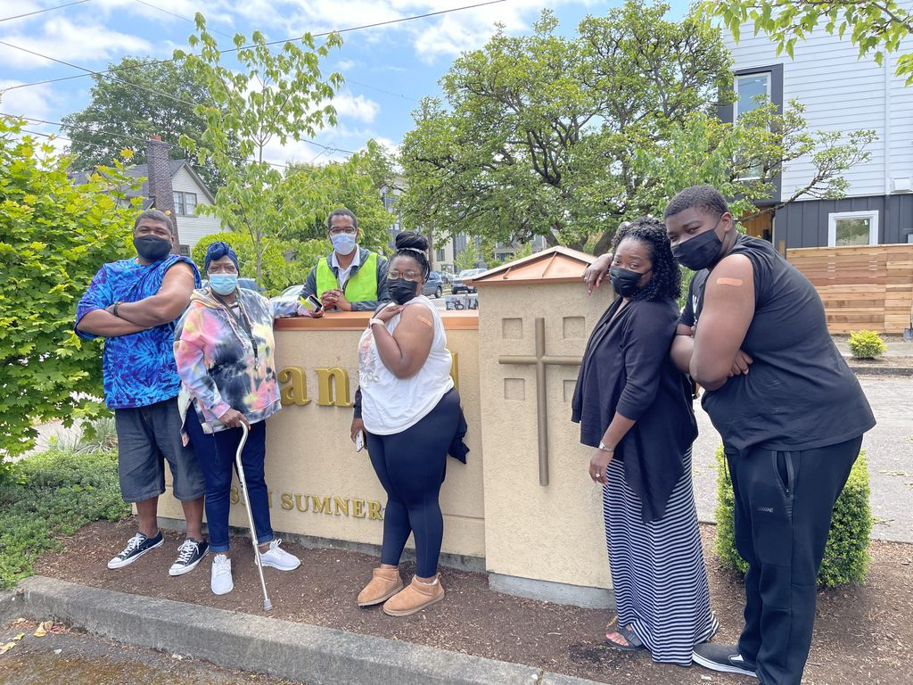 Five members of a family gather with Dr. Donn Spight from the OHSU Vaccine Equity Committee outside Emmanuel Church, showing off the Band-aids on their upper arms after the family members got vaccinated.