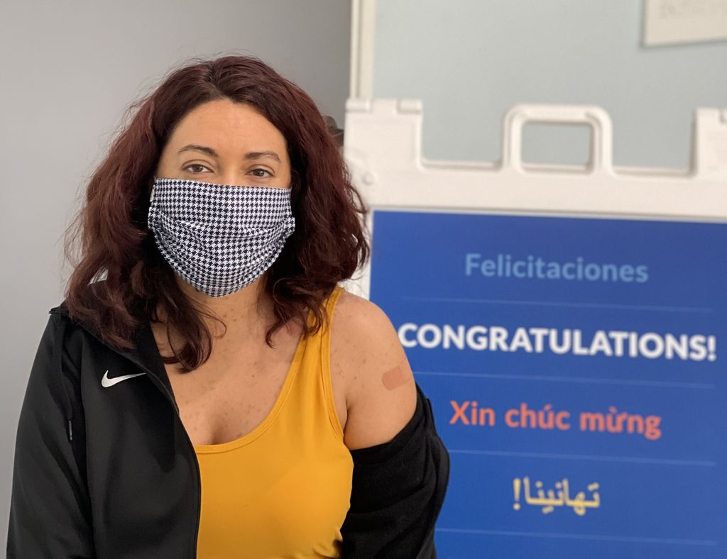 Young woman who just got vaccinated shows the Bandaid on her upper arm in front of a multilingual sign congratulating patients.