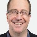 Close-in head shot of Eric Dishman, a smiling adult Caucasian man in glasses.