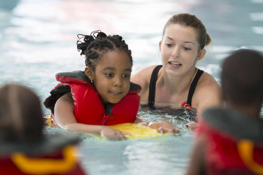 A multi-ethnic group of elementary age children are learning how to swim at the public pool. One little girl is holding onto a kick board and is swimming through the water.