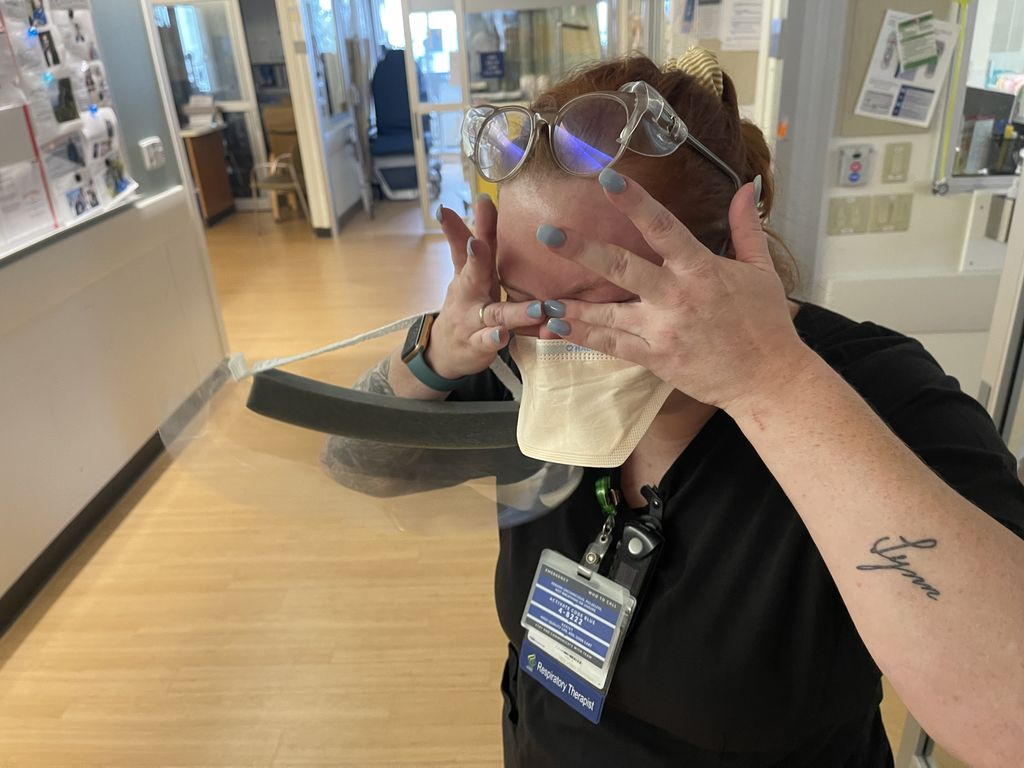 A crying nurse wipes their eyes around protective eyewear, and a face mask; she has a clear plastic face shield hanging from her arm.