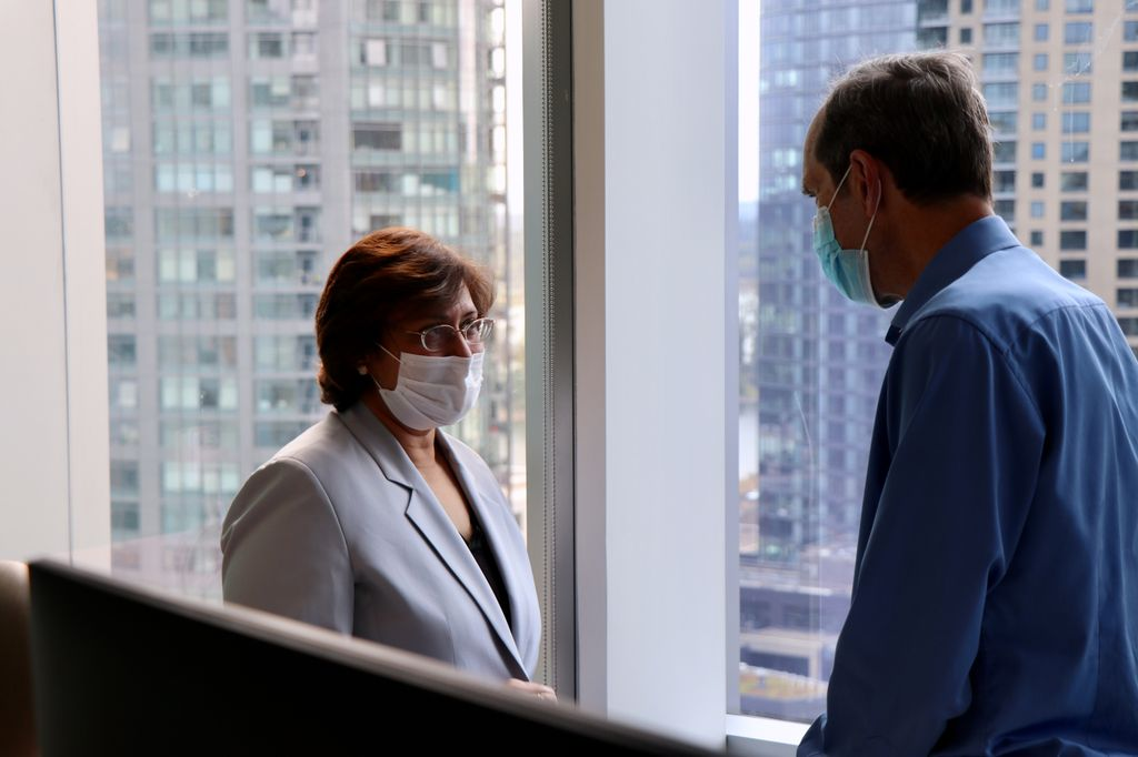 A tall man seen in profile speaks to a shorter woman; both wear surgical masks.