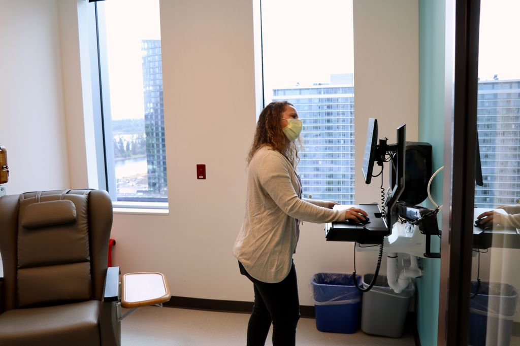 A nurse with long, wavy hair looks at a computer monitor in OHSU's cancer research unit.