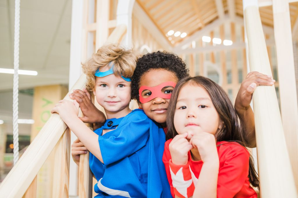 Intercultural little friends in costumes sitting on staircase in front of camera while playing together in children room