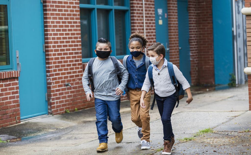 A group of three multi-ethnic elementary school students walking outside the school building, carrying backpacks, and wearing face masks. They are back to school during the covid-19 pandemic. The boy on the left is Hispanic. The one in the middle with long  hair tied back is mixed race African-American and Caucasian. And their friend on the right is mixed race Middle Eastern and Caucasian. They are 7, 10 and 8 years old.