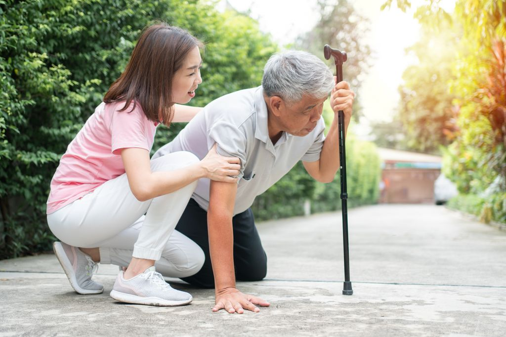 An elderly person falls on the sidewalk and another person is attempting to help them up.