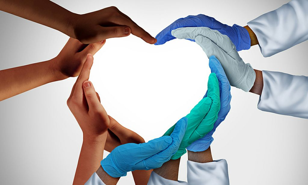 An image of multiple people's hands together forming a large heart shape.