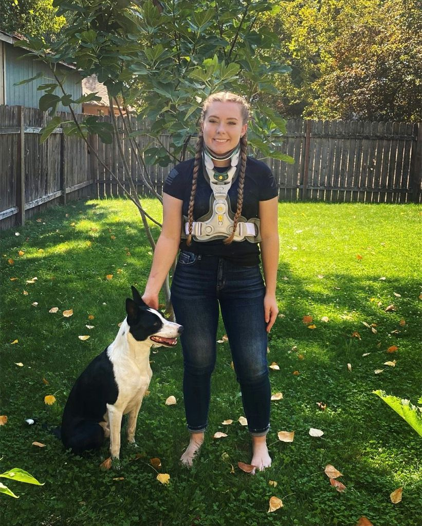 A woman named Marin Metz in a spine recovery brace stands on her lawn with her dog named Chief.
