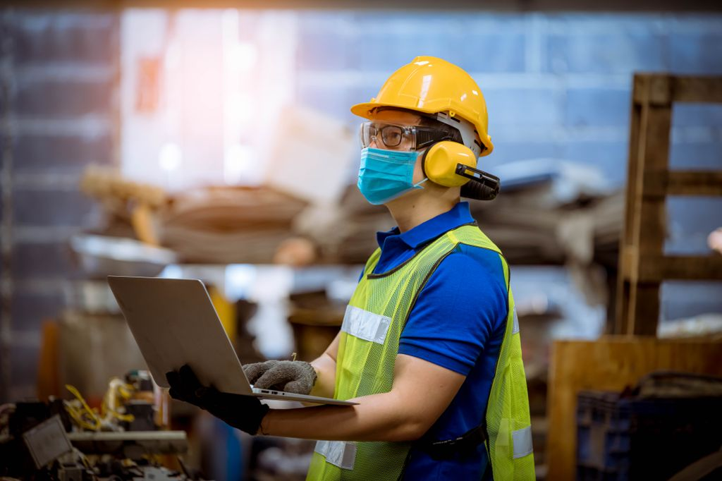 Portrait man worker under inspection and checking production process on factory station by wearing safety mask to protect for pollution and virus in factory.