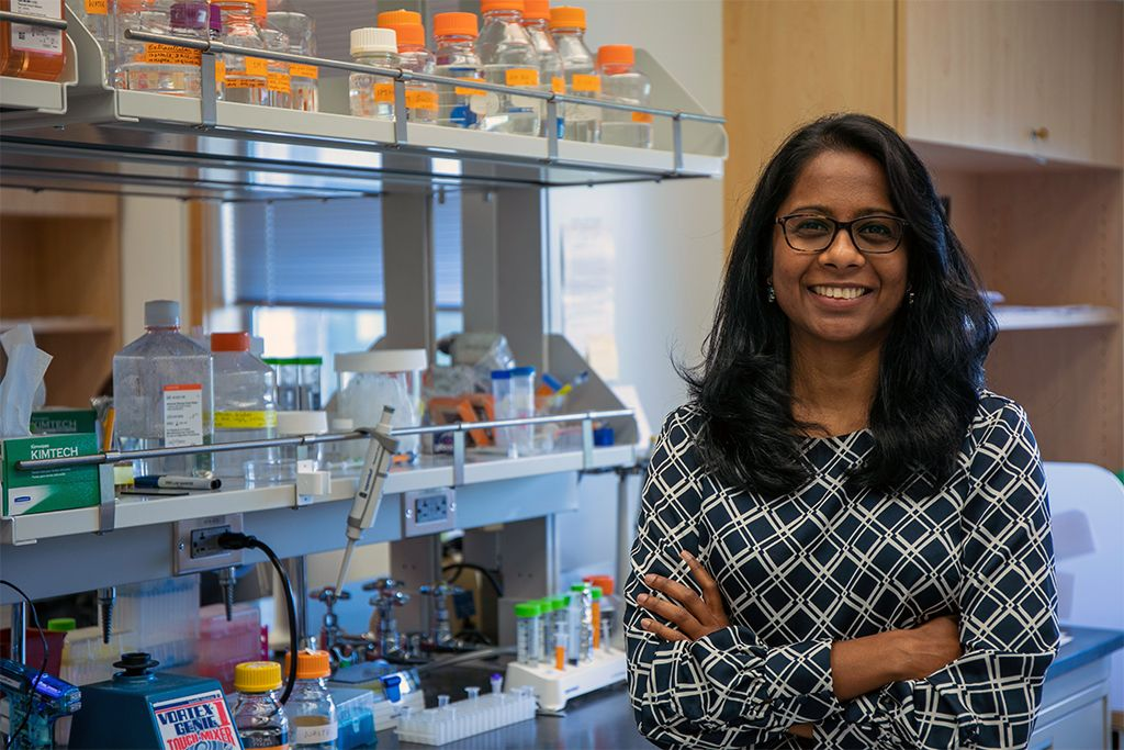 Swetha Murthy, Ph.D., a woman with dark hair, glasses, and a black and white diamond print top, stands next to equipment in her research lab at OHSU's Vollum Institute.