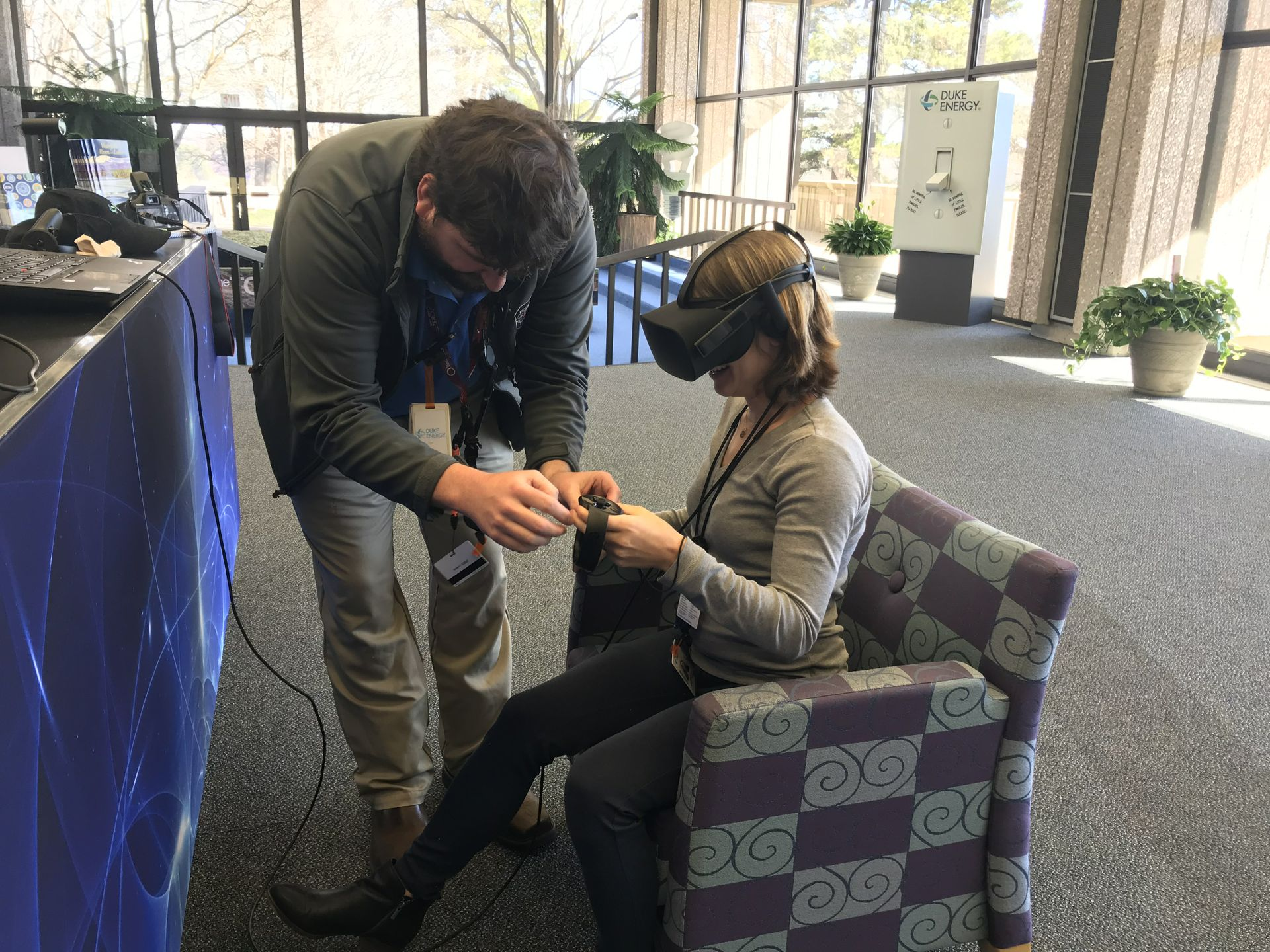Mikayla Kreuzberger (right) using a virtual reality headset with guidance from Brad Medlin (left) at Oconee Nuclear Station's World of Energy