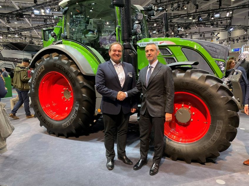 Two men in suits standing in front of a large green Fendt tractor at Agritechnica 2019, shaking hands and smiling