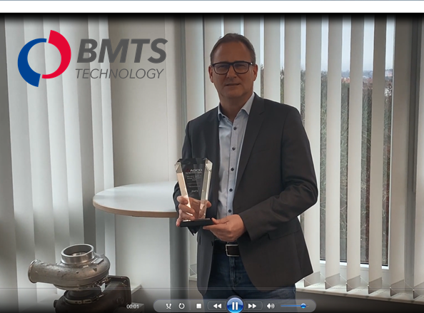 Smiling man in suit with glasses holding award next to exhaust turbocharger, in front of vertical blinds, logo superimposed