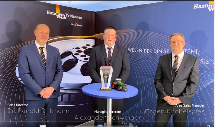 Three men in suits stand in a tradeshow booth; a small table holds an award and a model Fendt tractor.