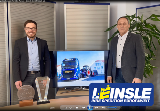 Two men in suits smile next to an LCD monitor showing a tractor-trailer towing a Fendt tractor; two awards on the table and logo superimposed
