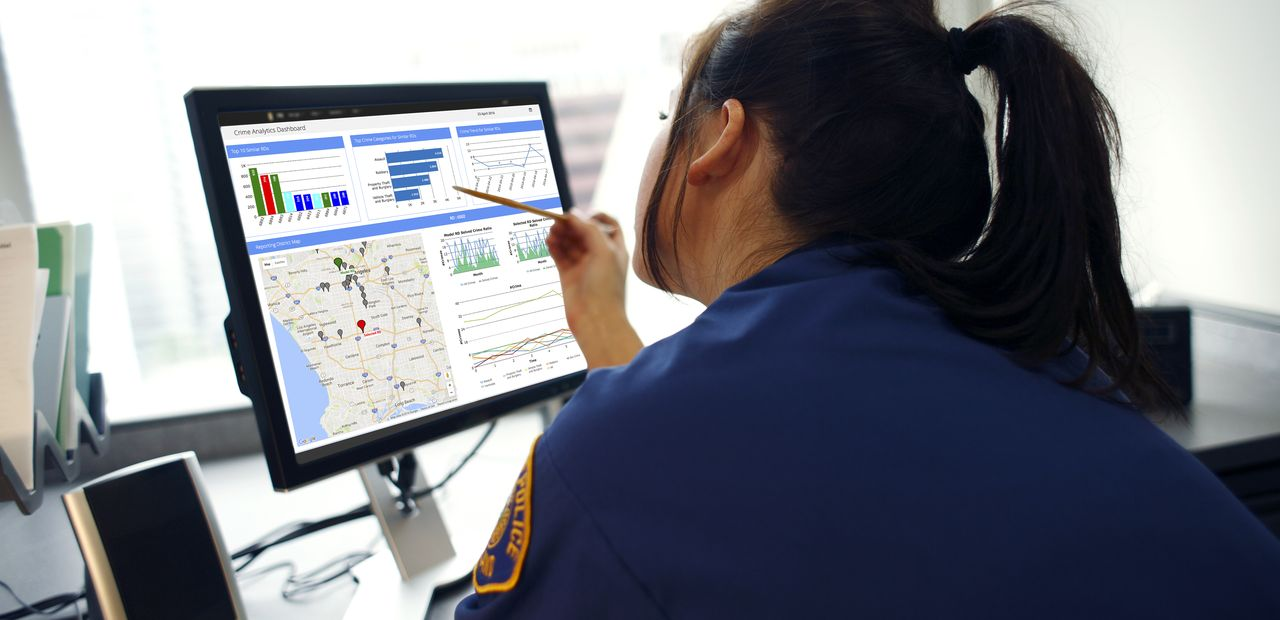 Police officer looking at crime forecasting data available through the Conduent Business Intelligence platform