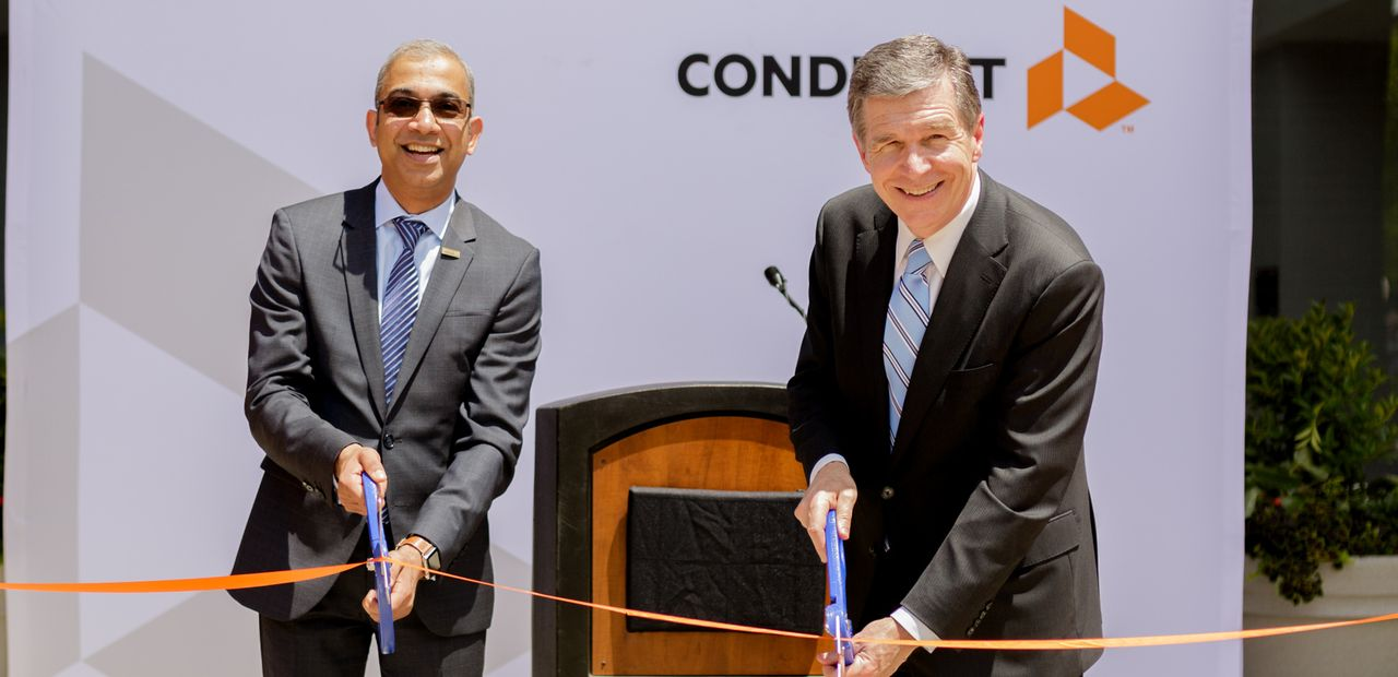 Conduent Incorporated's CEO Ashok Vemuri and North Carolina Governor Roy Cooper celebrate the opening of Conduent's technology and innovation hub in Morrisville, N.C.