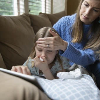 Mother checking forehead temperature of sick daughter laying on sofa