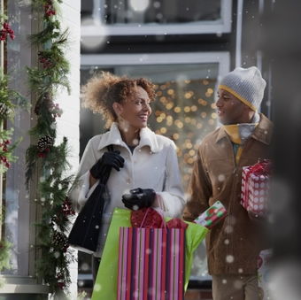 Couple carrying Christmas gifts outdoors