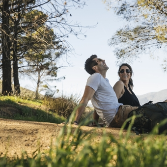 Couple relaxing on dirt footpath while hiking