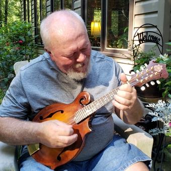 Tom Sharpe plays the mandolin at his home in Winston-Salem.