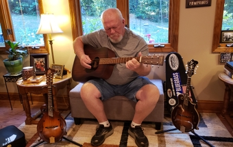Tom Sharpe plays the guitar at his house in Winston-Salem