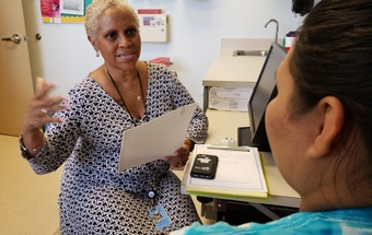 Milagros Amaro works with a patient at the health department 2