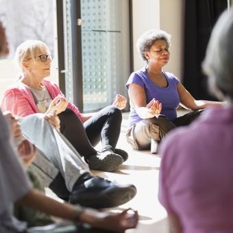 Serene active seniors meditating in circle
