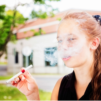 Preteen girl tries e-cigarette with her friend